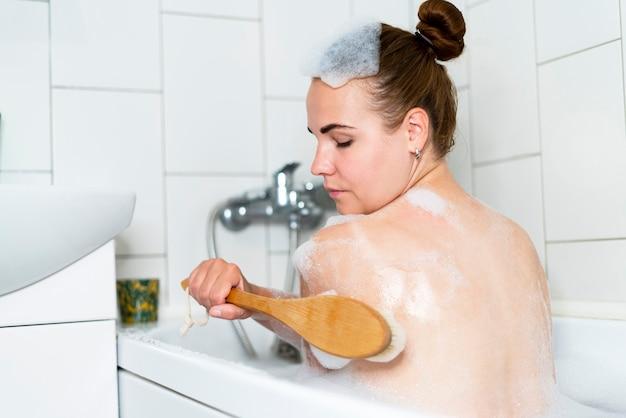 浴室の女の子の泡で泡風呂を取っている美しい女性の美の肖像画は彼女をこすっています
