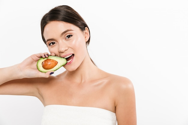 噛んで、白で分離された新鮮な熟したアボカドの半分を食べるブルネットのアジアの女性の美しさの肖像画