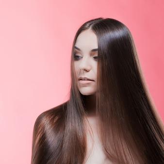 Портрет красоты брюнет с совершенными волосами, на розовой стене. уход за волосами