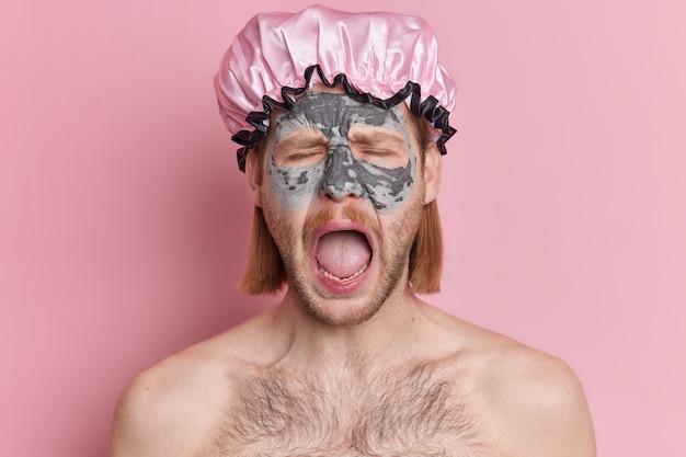 감정적 인 남자의 아름다움 초상화는 입을 크게 벌리고 피부 회춘을 위해 클레이 마스크를 적용하여 목욕 모자 스탠드를 벗은 채로 감정적으로 외칩니다.
