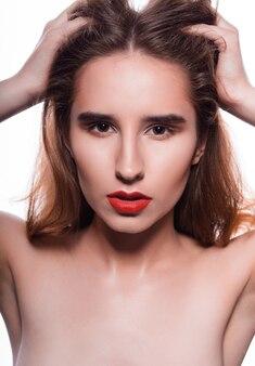 完璧な肌と赤い唇を持つファッショナブルなブルネットモデルの美しさの肖像画。白い背景で撮影したスタジオ