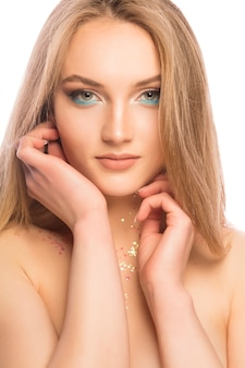 白い背景の上に明るく輝くメイクと華やかなブロンドの女性の美しさの肖像画