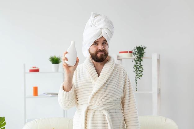 바디 크림 로션 튜브를 들고 수건과 목욕 가운에 잘생긴 아름 다운 남자의 아름다움 초상화