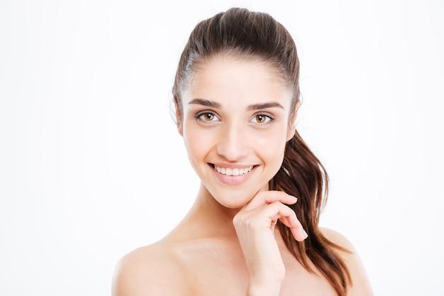 흰 벽에 서서 웃고 있는 행복한 젊은 여성의 아름다움 초상화