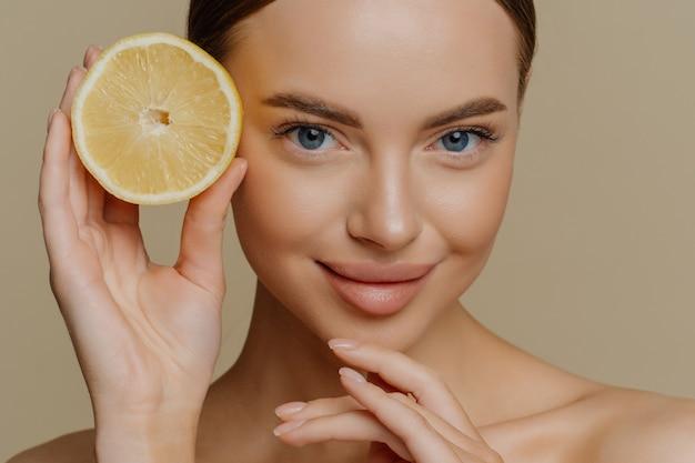Красота портрет здоровой молодой женщины топлес брюнетка касается подбородка, нежно держит половину сочного свежего лимона