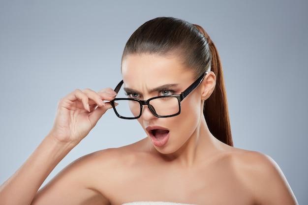 積極的に脇を見ている眼鏡をかけたイライラした女の子の美しさの肖像画。口を開けて、眼鏡に触れて、見つめている怒っている女性の頭と肩