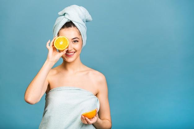 Красавица портрет радостной привлекательной полуголой женщины с полотенцем, обернутой вокруг ее лица, держащей дольки апельсина на лице и смотрящей в камеру
