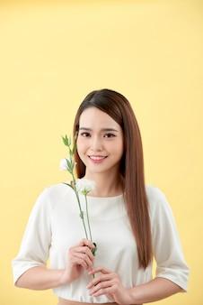 노란색 배경 위에 흰색 lisianthus 꽃을 들고 있는 20대 여성의 아름다움 초상화