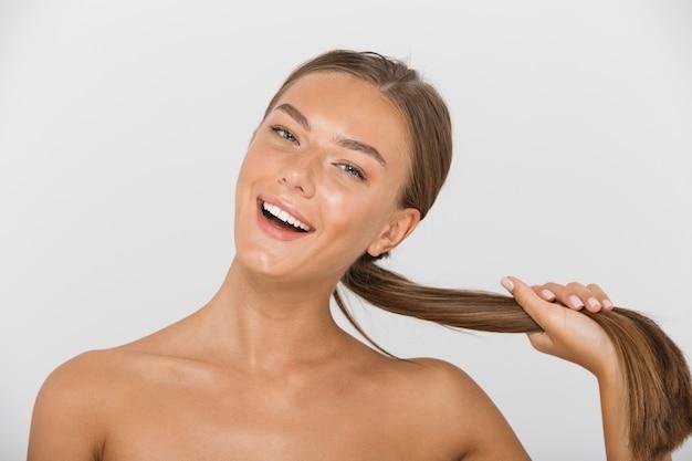 Портрет красоты прекрасной женщины без рубашки с длинными каштановыми волосами, улыбающимися, изолированными