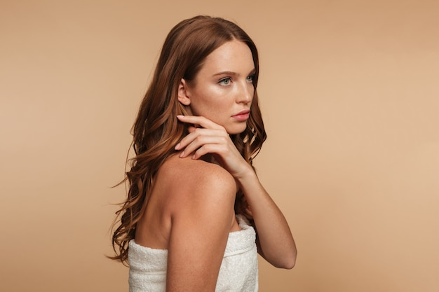 Портрет красоты загадочной рыжеволосой женщины с длинными волосами, завернутыми в полотенце, позирует в сторону и смотрит в сторону Бесплатные Фотографии