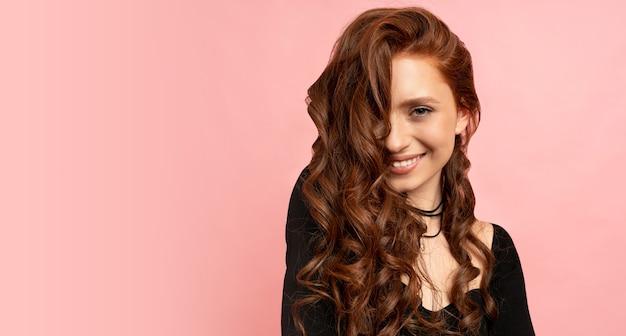 ピンクの壁を越えてポーズをとる赤い頭の女性の美しさの肖像画。ウェーブのかかった髪。満面の笑み。