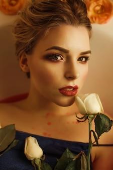 완벽한 화장을 한 매혹적인 금발 여성의 미인 초상화는 붉은 물과 흰 장미로 목욕을 한다