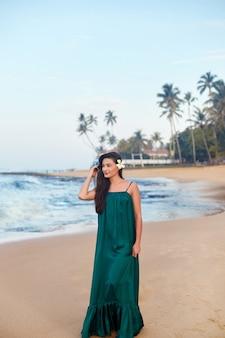 海沿いの緑のドレスで笑顔の女性の美しさの肖像画。海辺に立って目をそらしている幸せな美しい女性。