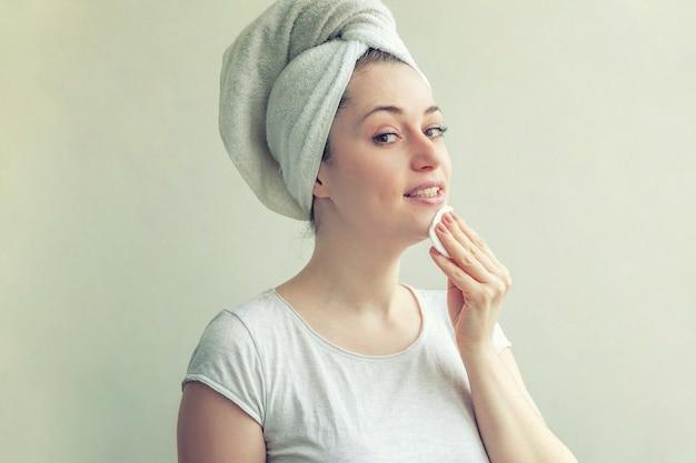 흰색 배경에 격리된 면 패드로 화장을 제거하고 부드러운 건강한 피부를 가진 머리에 수건을 쓴 웃는 여성의 아름다움 초상화. 스킨케어 클렌징 스파 릴랙스 컨셉