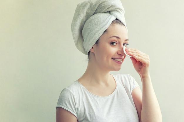 Портрет красоты улыбающейся женщины в полотенце на голове при извлечение мягкой здоровой кожи составляет при ватный диск, изолированные на белом фоне. концепция ухода за кожей, очищающая спа, релакс