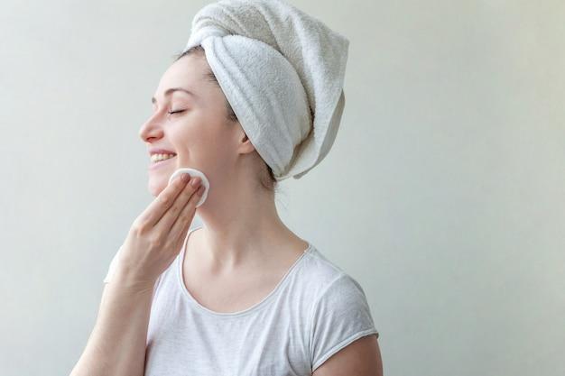 Портрет красоты улыбающейся женщины в полотенце на голове при извлечение мягкой здоровой кожи составляет при ватный диск, изолированные на белом фоне.