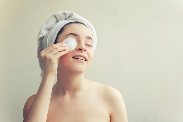 Портрет красоты усмехаясь женщины в полотенце на голове с извлекать мягкой здоровой кожи составляет при изолированная пусковая площадка хлопка на белизне. очищающий спа-салон relax relax