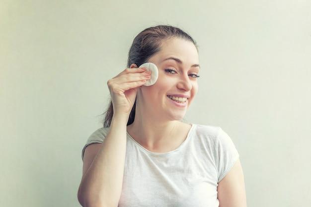 흰색 배경에 격리된 면 패드로 화장을 제거하고 부드러운 건강한 피부를 가진 웃는 여성의 아름다움 초상화. 스킨케어 클렌징 스파 릴랙스 컨셉
