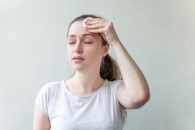 Портрет красоты усмехаясь женщины с извлечением мягкой здоровой кожи составляет при ватный диск изолированный на белой предпосылке.