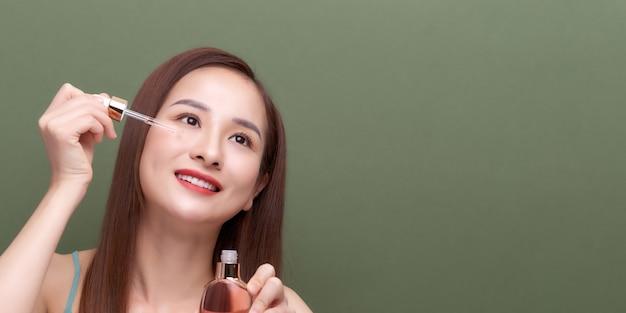 Портрет красоты улыбающейся девушки молодой женщины, держащей пипетку с косметическим маслом или сывороткой возле чистого лица.