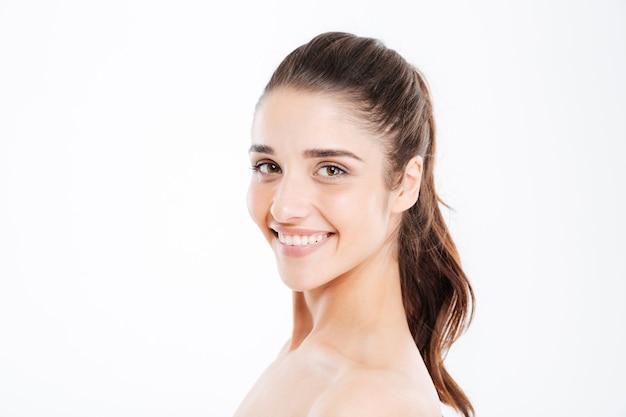 흰 벽 너머로 정면을 바라보며 웃고 있는 젊은 여성의 아름다움 초상화