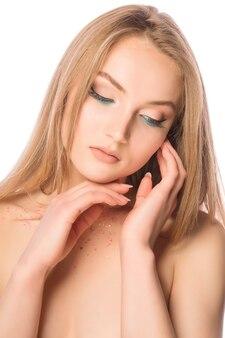 彼女の首にキラキラと明るいメイクで優しい若いモデルの美しさの肖像画。クローズアップショット