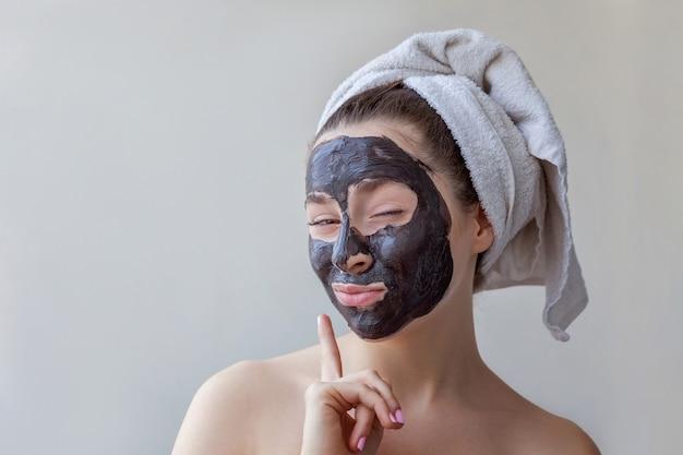 顔に黒い栄養マスクを適用し、白い背景を分離した頭にタオルで女性の美しさの肖像画。スキンケアクレンジングエコオーガニックコスメティックスパリラックスコンセプト