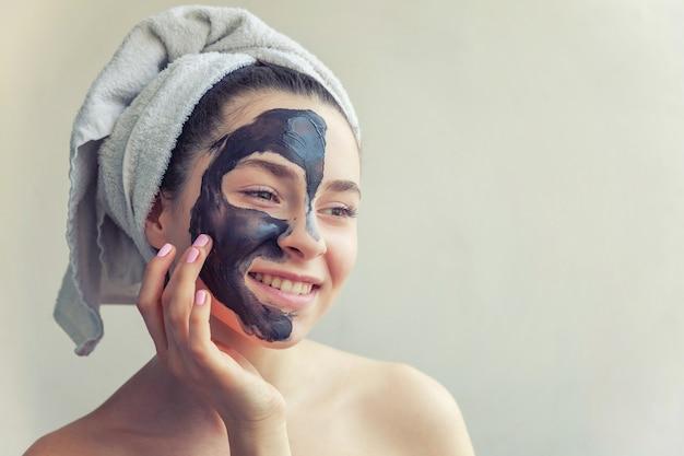 머리에 수건을 쓴 여성의 아름다움 초상화는 얼굴에 검은 영양 마스크를 바르고 흰색 배경이 격리되어 있습니다. 스킨케어 클렌징 에코 유기농 코스메틱 스파 릴랙스 컨셉