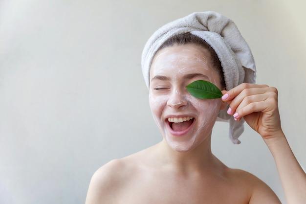 Красота портрета женщины в полотенце на голове с белой питательной маской или кремом на лице и зеленом листе в руке, белом фоне изолированы. уход за кожей очищающий эко органическая косметическая спа-концепция