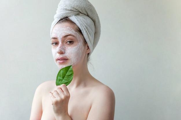 Красота портрета женщины в полотенце на голове с белой питательной маской или кремом на лице и зеленом листе в руке, белом фоне изолированы.
