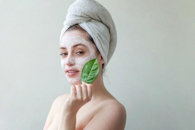 흰색 영양 마스크 또는 얼굴에 크림과 손에 녹색 잎, 흰색 배경에 고립 된 머리에 수건에 여자의 아름다움 초상화.