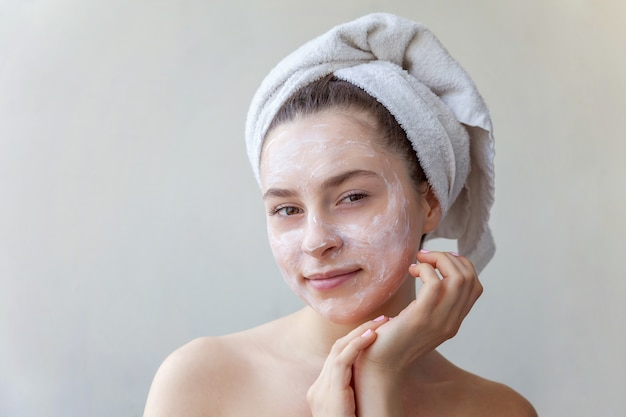 흰색 영양 마스크나 크림을 얼굴에 바르고 흰색 배경에 격리된 수건을 쓴 여성의 아름다움 초상화. 스킨케어 클렌징 에코 유기농 코스메틱 스파 릴랙스 컨셉