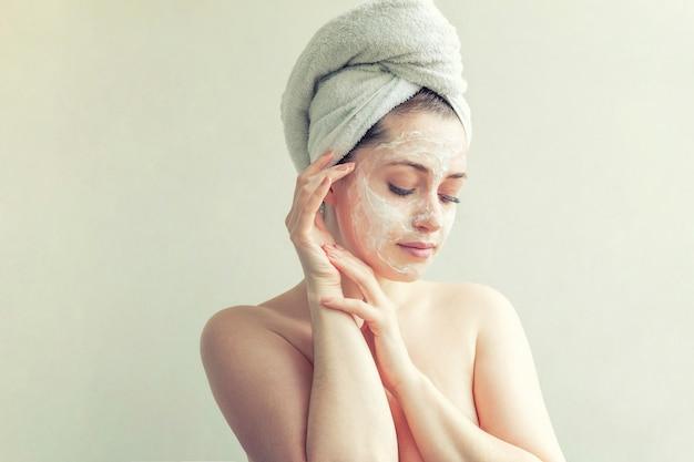 Портрет красоты женщины в полотенце на голове с белой питательной маской или кремом на лице, белом фоне изолированы. уход за кожей очищающий эко-органическая косметическая спа-концепция релаксации