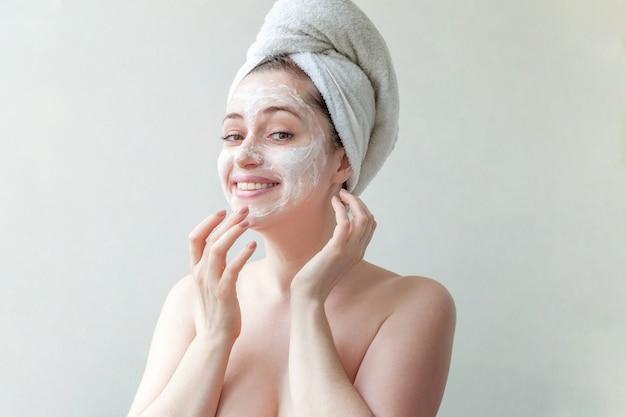 흰색 영양 마스크 또는 얼굴에 크림, 고립 된 흰색 배경 머리에 수건에 여자의 아름다움 초상화.