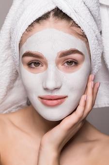 白い栄養マスクまたは顔、白い壁が分離されたクリームで頭の上のタオルで女性の美しさの肖像画。スキンケアクレンジングエコオーガニック化粧品スパリラックスコンセプト