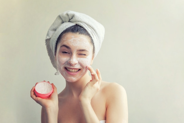 白い栄養マスクまたは顔、分離した白い壁にクリームを頭の上のタオルで女性の美しさの肖像画