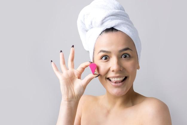 Красота портрета женщины в белом полотенце на голове с губкой для тела с учетом розового сердца. уход за кожей, очищающий экологическую органическую косметическую спа-концепцию релаксации.
