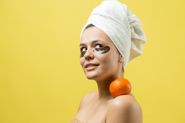 顔に金の栄養マスクと頭に白いタオルで女性の美しさの肖像画。スキンケアクレンジングエコオーガニックコスメティックスパリラックスコンセプト。オレンジ色のみかんを背負って立っている女の子。