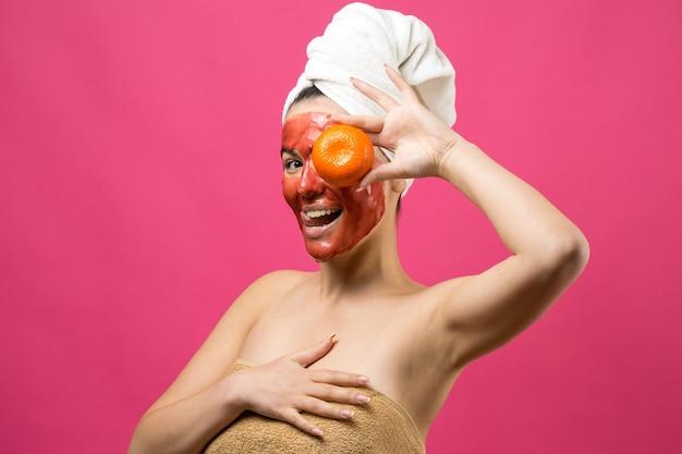 顔に赤い栄養マスクと頭に白いタオルで女性の美しさの肖像画。スキンケアクレンジングエコオーガニックコスメティックスパリラックスコンセプト。オレンジ色のみかんを背負って立っている女の子。