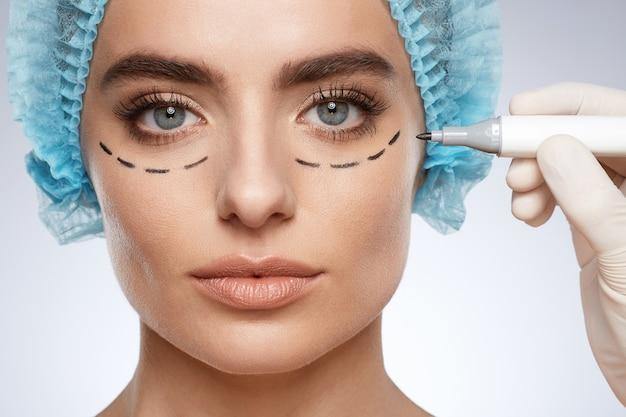 カメラ、整形手術のコンセプト、スタジオを見ている女性の美しさの肖像画。目の下に穿刺線、マーカーで白い手袋の描画線を手で青い帽子のモデルのクローズアップ