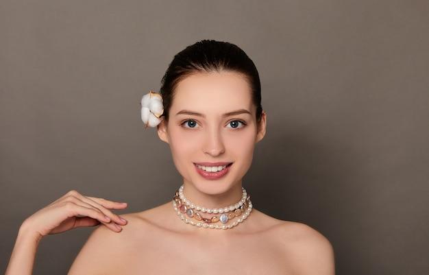 Красота портрет женщины с цветком на волосах и жемчужным ожерельем на коричневом фоне