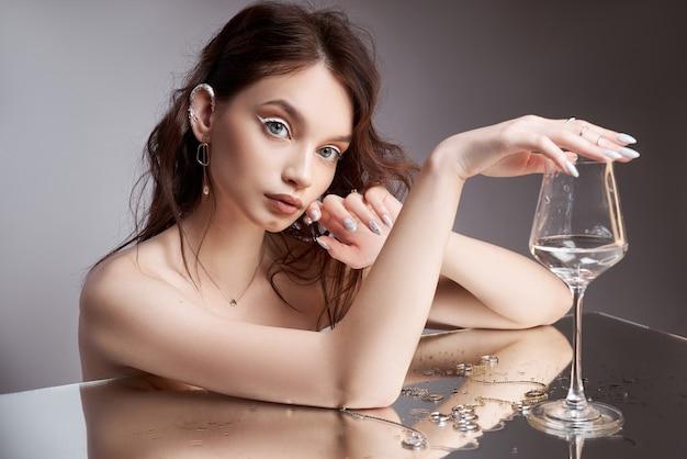 손에 유리를 가진 여자의 아름다움 초상화. 반지는 거울 테이블에 있습니다. 천연 화장품