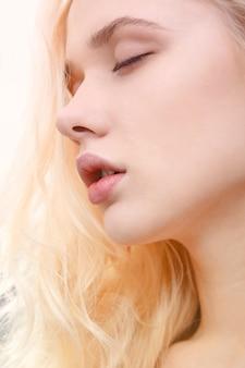 目を閉じてポーズをとって若い美しいブロンドの女性の顔の美しさの肖像画