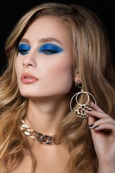 青い煙のような目で若いブロンドの女性の美しさの肖像画は、黄金色の宝石を身に着けていると彼女のイヤリングに触れることを占めています。ファッションメイク。