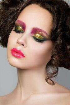 Портрет красоты молодой модели брюнетки с творческим современным жидким латексным макияжем