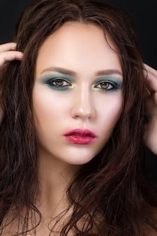 ファッションメイクの少女の美しさの肖像画。緑と金のスモーキーな目とぼやけた輪郭の赤い唇