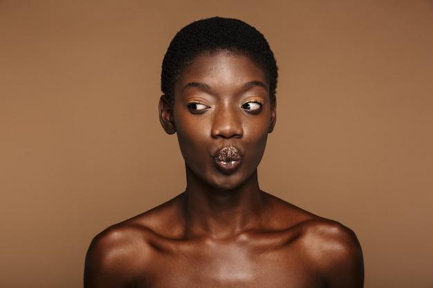ベージュで隔離の短い黒髪の若い半裸のアフリカの女性の美しさの肖像画