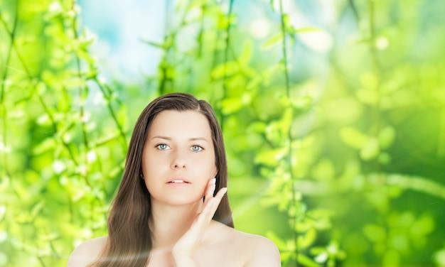 ウェルネス健康と有機的な美しさの概念だけでなく、背景に自然なスキンケアと化粧品ブランドの春の自然のための若い女性の美しさの肖像画
