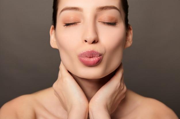 Красота портрет молодой женщины, делающей поцелуй лицо и руки на шее на светло-коричневом фоне
