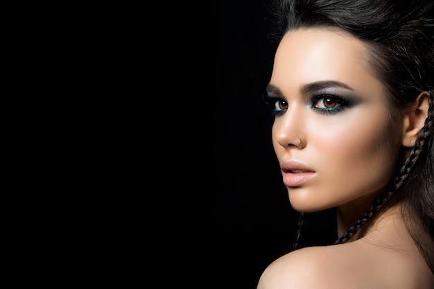 젊은 여자의 뷰티 초상화입니다. 완벽한 저녁 화장. 모델 포즈. 은색 스모키 눈. 클래식 메이크업 개념.
